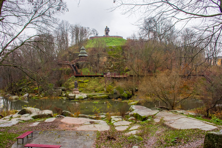 Hill near stone granite canyon of river Uzh in park with monuments to heroes and personalities of ancient Kievan Rus and ancient Drevlyanians amid of autumn gray rainy sky and wet weather in Korosten Stock Photo