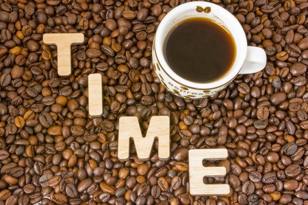 Idea of Coffee Time. Cup with brewed coffee is surrounded by roasted grains coffee tree with word time, made up of 3D wooden letters. Idea for time to drink refreshing drink in office, conferences
