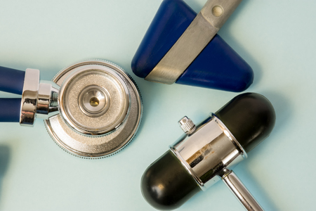 Stethoscope and two rubber heads of neurological reflex hammers close-up on a white background in the office of doctor of general medicine. Diagnostic medical tool