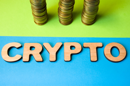 Concept of crypto and cryptocurrency coin front view. Word crypto composed of 3D letters in front of three stacks of coins, symbolizing cryptocurrency coins or mining process