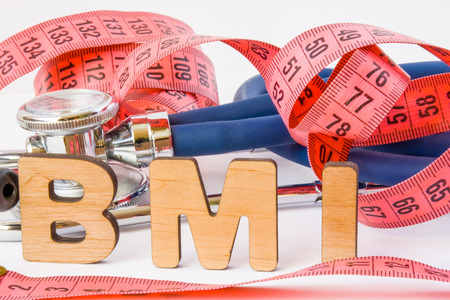 BMI or body mass index abbreviation or acronym photo concept in medical diagnostics or nutrition, diet. Word BMI is on background of tape to measure the circumference of body and medical stethoscope