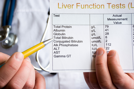 Doctor showing to patient or colleague on liver function test result LFT, standing in white medical coat. Concept photo to illustrate diagnostic and screening of liver diseases or disorders