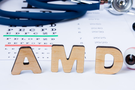 AMD Abbreviation or acronym of age-related macular degeneration - eye problem in older persons. Word AMD is on foreground near eye model with stethoscope and visual acuity test on blurry background Standard-Bild
