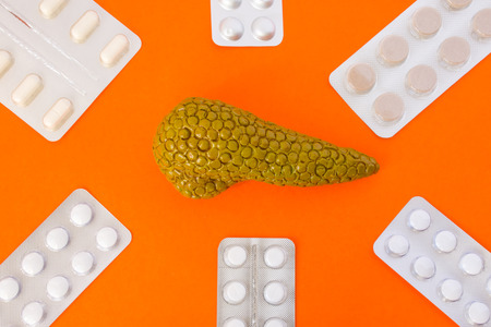 Model of pancreas gland surrounded by six blister packs with white pills on orange background.  Photo concept art of treatment or hormone, digestive enzyme or secretes replacement therapy of pancreas Stock Photo