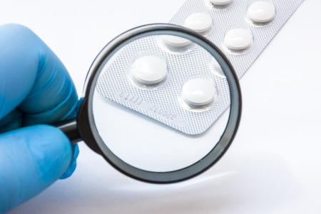 Prueba, verificación y determinación de la falsificación farmacéutica o el concepto de calidad de medicamentos y sustancias medicinales. Experto farmacéutico de verifica el número de cumplimiento de medicamentos