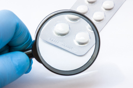 Testing, verification and determining pharmaceutical counterfeiting or fakes of medicines and medicinal substance quality concept. Pharmaceutical expert from checks number of medicine compliance Banco de Imagens