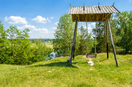 Beautiful rural landscape river Teteriv (Teterev). On steep mountain face steeper swing -  wooden structure with bench where children were playing, in background - houses of village and river bed Stok Fotoğraf