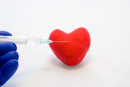 Injection into heart or cardiovascular disease treatment concept photo. Doctor holds in his hand, dressed in glove, syringe with medication and is preparing to make injection in shape card red heart Stok Fotoğraf