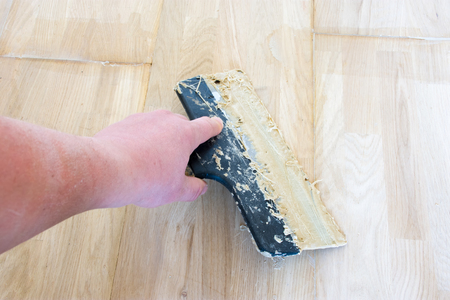 Carpet fitter master or floor person holding a spatula with wooden glue that is on the laid parquet. Photo scene from carpenter workplace and specialist of wood flooring