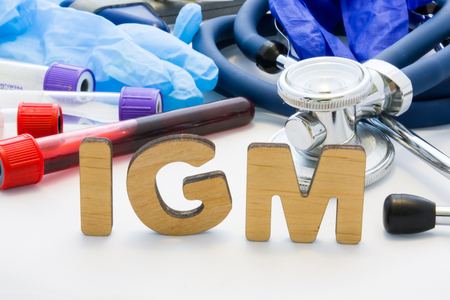 Medical abbreviation IGM in laboratory diagnostics. Letters, create words IGM, meaning Immunoglobulin M Medical, are surrounded by test tubes with blood, stethoscope and other medical equipment Stok Fotoğraf