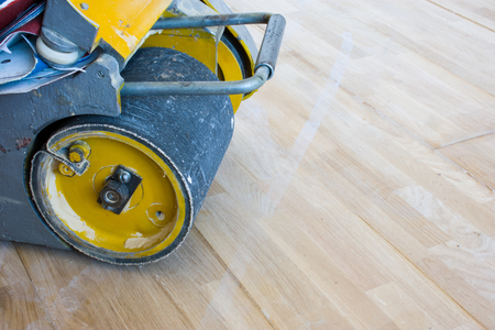 Scraping machine or grinder for the process of scraping wood parquet or other type of floor stands at just laid parquet and ready for use. Photo from carpenters work