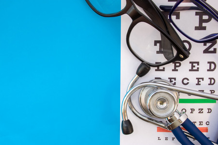 Snellen chart with pair of eyeglasses and stethoscope on blue background occupy half of photo, in second half empty space for titles. Concept photo of check visual acuity, optometry and ophthalmology