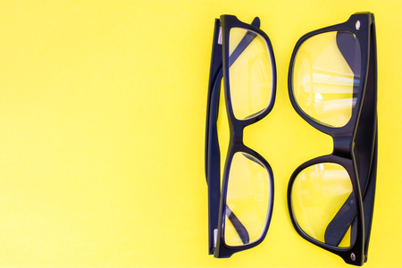 Two black eyeglasses on yellow uniform background view from above with the clear area of half photo for labels, headers. Concept photo of selection of glasses, optometrist work, shop of prescription