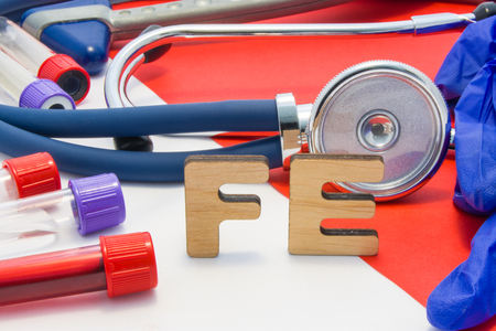 FE medical abbreviation meaning total iron or ferrum in blood in laboratory diagnostics on red background. Chemical name of FE is surrounded by medical laboratory test tubes with blood, stethoscope Reklamní fotografie