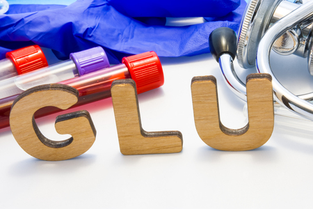 GLU abbreviature mean Glutamate amino icid with lab tubes with blood and stethoscope. Using acronym GLU in laboratory clinical diagnosis, determination of pathologies contacts to increase Stok Fotoğraf