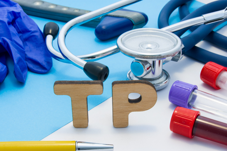 TP Medical lab acronym, meaning total protein in blood or serum. Letters that make word of TP, located near test tubes with blood, stethoscope and other diagnostic tools and devices, latex gloves