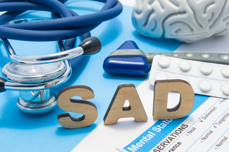 SAD medical abbreviation meaning seasonal affective disorder, depression could during seasons with little light. Word SAD is surrounded by stethoscope, result of mental status exam, drugs and brain