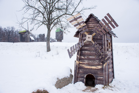 Small wooden windmill in foreground with focus on it and big historical windmills in background against background of winter landscape with deep snow and forest on horizon. European rural scene