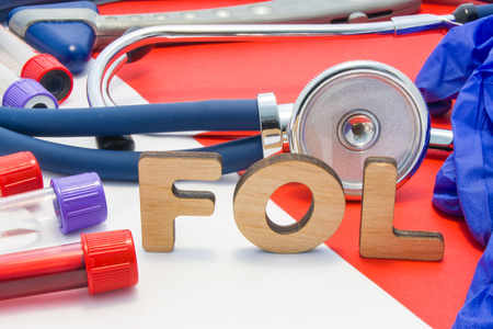 FOL medical abbreviation meaning total folate or folic acid in laboratory diagnostics on red background. Chemical name of FOL is surrounded by medical laboratory test tubes with blood, stethoscope Stok Fotoğraf - 118411110
