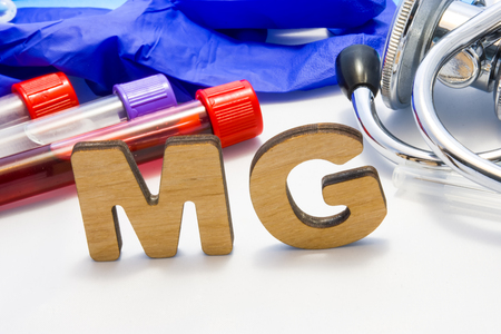 MG abbreviature mean Magnesium electrolyte with lab tubes with blood and stethoscope. Using acronym MG in laboratory clinical diagnosis, determination of pathologies contacts to deficiency Stok Fotoğraf - 118411117