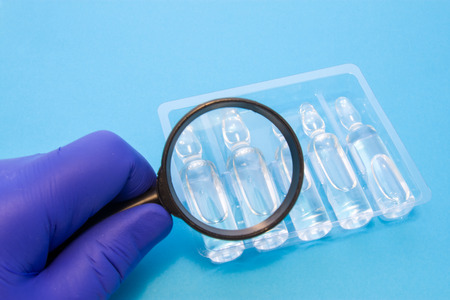 Quality control of liquid medicines in transparent vials concept photo. Quality Control Specialist of medicines and health products conducting product validation and analysis on purity and identity