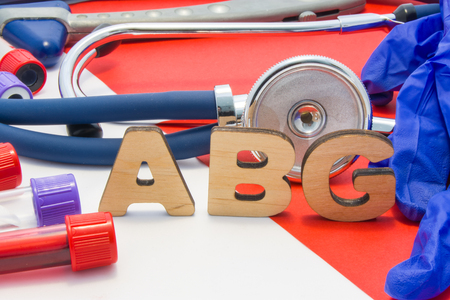 ABG medical abbreviation meaning arterial blood gas in blood in laboratory diagnostics on red background. Chemical name of ABG is surrounded by medical laboratory test tubes with blood, stethoscope