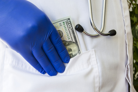 Doctor hides or lays down hundred dollar bill in pocket of white doctoral coat. Concept photo bribes, corruption in medicine, payment of medical care in private practice or public medicine, wages Stok Fotoğraf