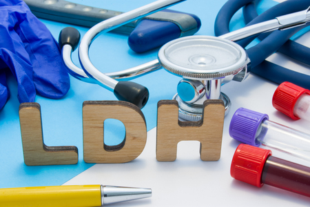 LDH Medical lab acronym, meaning lactate dehydrogenase. Letters that make word of LDH, located near test tubes with blood, stethoscope and other diagnostic tools and devices, latex gloves Stok Fotoğraf