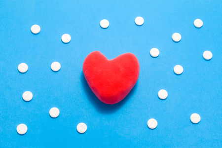 3D anatomical model of heart is on blue background surrounded by white pills as ornament polka dots. Medical concept by pharmacological tableted treating of heart and vessel disease, pharmacotherapy Stok Fotoğraf