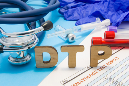 Concept photo DTP (or DPT) - diphtheria, tetanus, pertussis - vaccine or vaccination process of children. Abbreviation DTP is against background of ampoule with vaccine, syringe, stethoscope, blood Stok Fotoğraf