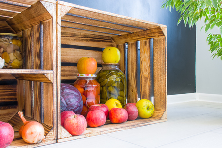 Apples, cabbage and pickled cucumbers and tomatoes in jars are in a wooden box on background of black wall in kitchen. Aesthetic open storage of products or stocks of food in context of modern kitchen