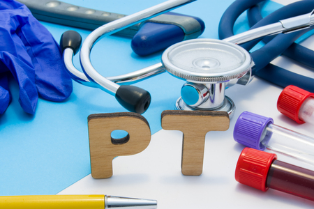 PT Medical lab acronym, meaning Prothrombin Time in blood. Letters that make word of PT, located near test tubes with blood, stethoscope and other diagnostic tools and devices, latex gloves Stok Fotoğraf