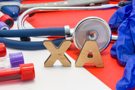 XA medical abbreviation meaning LMW heparin in blood in laboratory diagnostics on red background. Chemical name of XA is surrounded by medical laboratory test tubes with blood, stethoscope, gloves Stok Fotoğraf