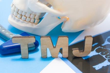 TMJ abbreviazione medica di articolazione temporomandibolare. Lettere ATM circondate da teschio umano con mascella inferiore, martello neurologico e radiografie. Concetto di anatomia, patologia dell'articolazione temporomandibolare