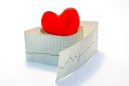 Idea photo arrhythmias and heart diseases related to disorders of normal heart rhythm. Model red heart lies on top of the roll of paper electrocardiogram on a white background