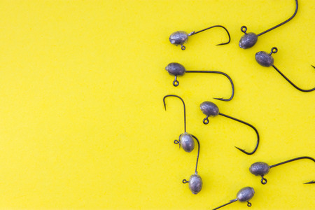 Fishing jig heads with hooks lie on a yellow background view from above with the clear area of half photo for labels, headers. Concept photo for to prepare for fishing, fishing tackle