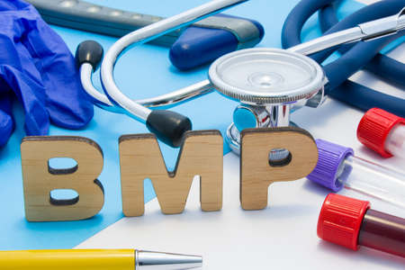 BMP Medical laboratory acronym, meaning Basic Metabolic Panel. Letters that make word of BMP, located near test tubes with blood, stethoscope and other diagnostic tools and devices, latex gloves