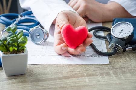 Medico di medicina interna e cardiologo che tiene tra le mani e mostra al paziente la figura del cuore del cartellino rosso durante la consultazione medica. Spiegazione delle cause del cuore, diagnosi e trattamento