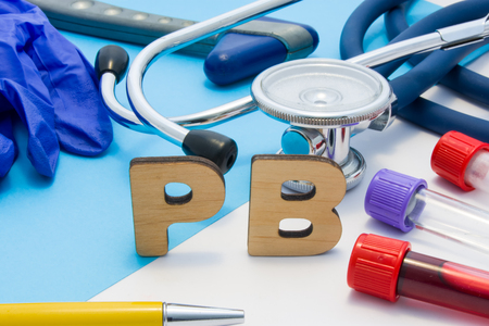 PB Medical lab acronym, meaning lead or plumbum in human body. Letters that make word of PB, located near test tubes with blood, stethoscope and other diagnostic tools and devices, latex gloves