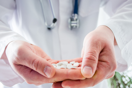 Doctor keeps in folded palms pills in foreground with focus on drugs, on background blurred body in white robe with phonendoscope. Concept pharmacological treatment, drug of last resort, accessibility