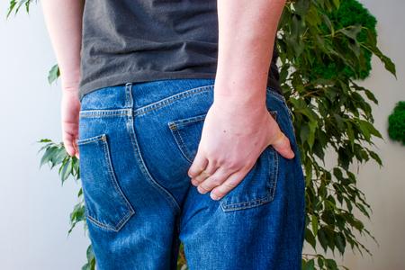 Der Mann hält die Hand am unteren Teil des Gesäßes. Konzeptfotomanifestationen von Schmerzen am Ausgang des Ischiasnervs, Entzündungen, Ischias oder Osteochondrose der Wirbelsäule, Schmerzen im Gesäßmuskel, Rektum oder Anus