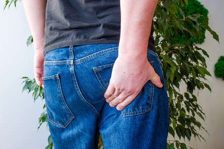 Man keeps hand on lower part of buttocks. Concept photo manifestations of pain at exit of sciatic nerve, inflammation, sciatica or osteochondrosis of spine, pain in gluteus muscle, rectum or anus Reklamní fotografie