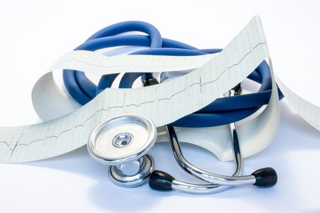 Diagnosis, treatment and prevention of diseases of heart and cardiovascular system concept photo. Blue stethoscope is surrounded by tape of ECG with electrocardiogram drawn on it. Diagnosis of disease Standard-Bild