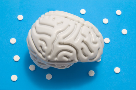 3D anatomical model of brain is on blue background surrounded by white pills as ornament polka dots. Medical concept by pharmacological tablet treating brain diseases, pharmacotherapy, chemotherapy Stok Fotoğraf