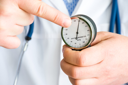 Doctor shows to patient and points finger at arrow of mechanical sphygmomanometer, which in turn indicates high number of blood pressure. Concept photo treatment and prevention of elevated pressure