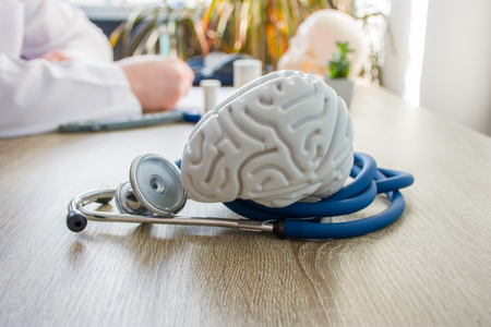 Concept photo of diagnosis and treatment of brain nervous. In foreground is model of brain near stethoscope on table in background blurred silhouette doctor at table, filling medical documentation