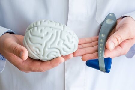 Doctor or scientist holds in one hand figure of brain in another - neurological reflex rubber hammer. Concept photo of neurology, neurosurgery and neuroscience, study of human nervous system, thinking