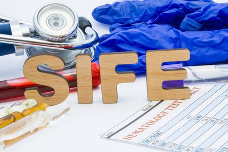 SIFE laboratory medical abbreviation serum immunofixation electrophoresis concept photo. On table is laboratory acronym SIFE next to tubes of blood, other biological fluids, result analysis