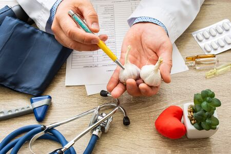 Doctor nutritionist during consultation held in his hand and shows patient garlic bulb. Counseling and explanation of use of garlic in food and diet, health benefits, effect on body and organs, immune