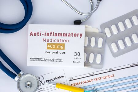 Anti-inflammatory medication or drug concept photo. On doctor table lies open packaging labeled Anti-inflammatory and fell out of her blisters with pills for treatment Imagens